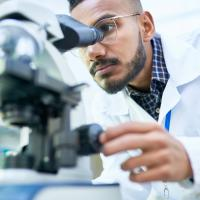 Photo of a scientist looking into a microscope