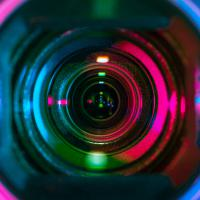 Closeup of a video camera lens, reflecting multicolored stage lights