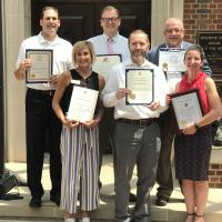A group of people holding award certificates