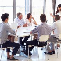 Group of non-employees gather around a table for a training session