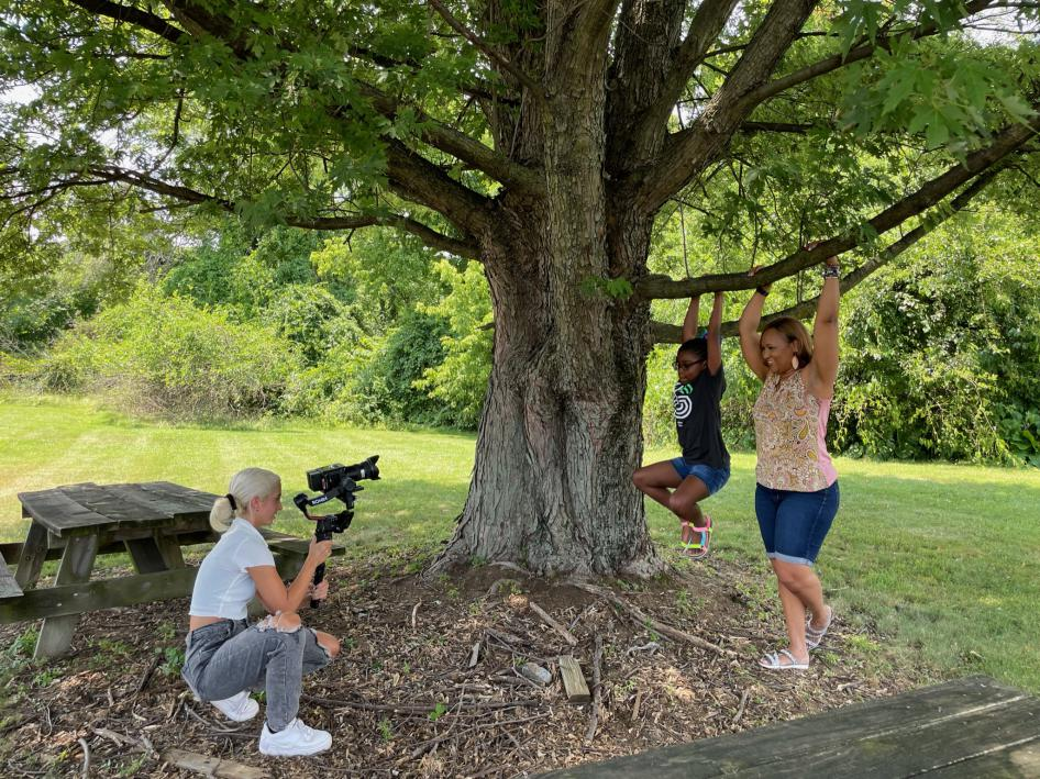 Photo of a young woman taking video of a girl and a woman hanging from a tree brnach